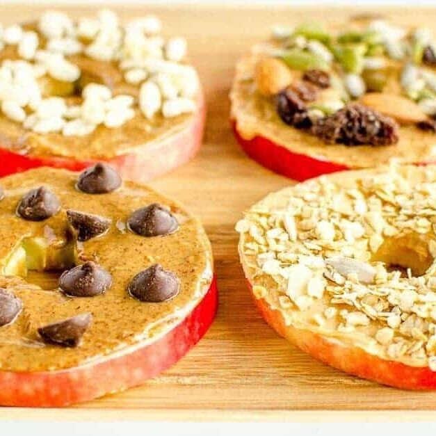 Four types of apple snacks are shown all all have a nut butter base with healthy toppings.